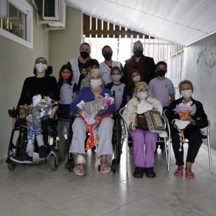 Crianças e professoras posam para foto com idosos após homenagens. Crianças posam para foto após homenagearem idosos. [Foto: Paulo Ribeiro].