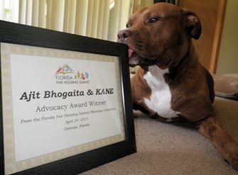 KANE, the pitbull, licks the Advocacy award that he and Ajit Bhogaita were given at the 2015 Florida Fair Housing Summit