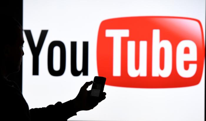 Ein Mann mit Smartphone steht vor dem Logo der Internet-Videoplattform Youtube. Seit anderthalb Jahrzehnten gibt es Youtube. Foto: Carsten Rehder/Dpa