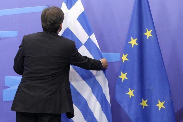 Der Rettungsfonds wird zurecht gerückt: Mann vor den Flaggen Griechenlands und der EU beim Treffen der Finanzminister.