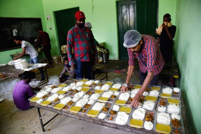Food being arranged in plates for migrant workers sheltered at a relief camp set up at a school on Day 7 of the 21-day nationwide lockdown imposed as a measure to contain the spread of  ...