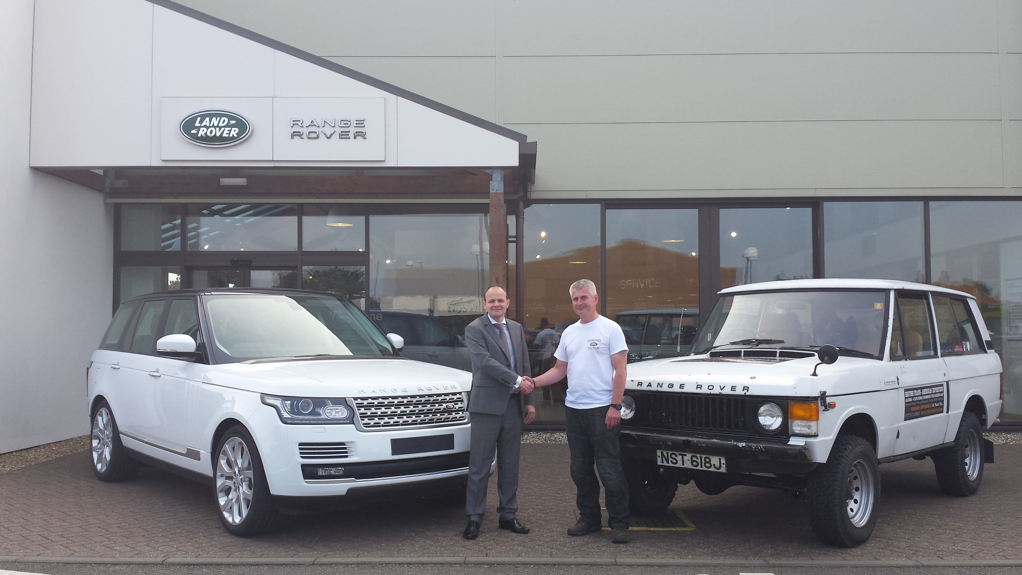 "Land Rover dealer Hunters of Norwich boss, Adrian Brooks stands by the newest model of Range Rover and shakes the hand of Richard Steven who stands by his 1970 RR ""Pearl"",one of the earliest ever built,at the start of his circumnavigation of mainland Great Britain commemorating 45 years of RR"