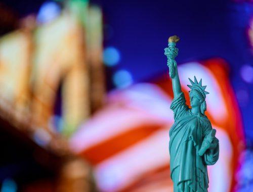 Statue of Liberty, United Stated flag background, Brooklyn Bridge New York, USA