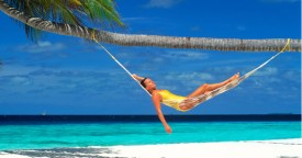 Woman relaxing in hammock under palm tree over white sandy beach in Maldive Islands. Image shot 10/2000. Exact date unknown.