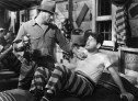 Full shot of Paul Muni as James Allen/Allen James laying on a bed while guard is standing over him PHOTOGRAPHS TO BE USED SOLELY FOR ADVERTISING, PROMOTION, PUBLICITY OR REVIEWS OF THIS SPECIFIC MOTION PICTURE AND TO REMAIN THE PROPERTY OF THE STUDIO. NOT FOR SALE OR REDISTRIBUTION. ALL RIGHTS RESERVED.