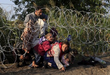 Syrian migrants cross under a fence as they enter Hungary at the border with Serbia, near Roszke, August 27, 2015. Hungary made plans on Wednesday to reinforce its southern border with helicopters, mounted police and dogs, and was also considering using the army as record numbers of migrants, many of them Syrian refugees, passed through coils of razor-wire into Europe.