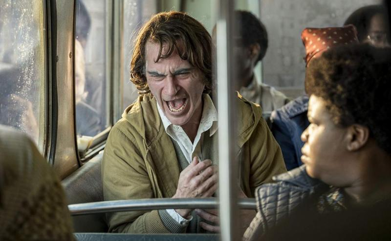 Arthur Fleck (Joaquin Phoenix) suffers on the bus