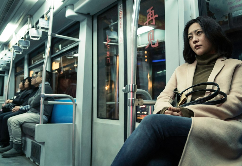 An asian woman, positioned on the right hand side, is sat on a subway ride. The woman has black hair, a beige long jacket and is holding a handbag.