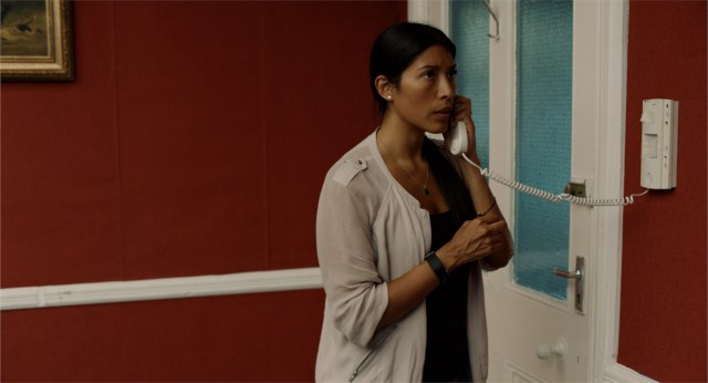 Image Description: A woman is standing, looking away from the camera as she is answering a landline phone. The woman has her hair tied up, and is wearing a black top with a white cardigan.