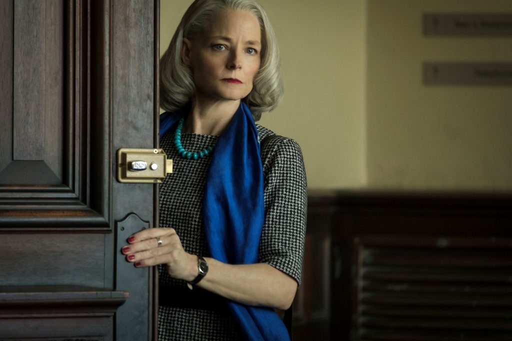 Image Description: A white woman stands, holding open a door and looking stern at the camera. The woman has grey hair, a black-and-grey dress and a blue scarf.