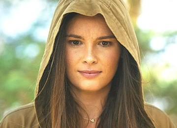 A woman wearing a brown hooded raincoat, looks down with a concerned expression. Behind is a treeline.