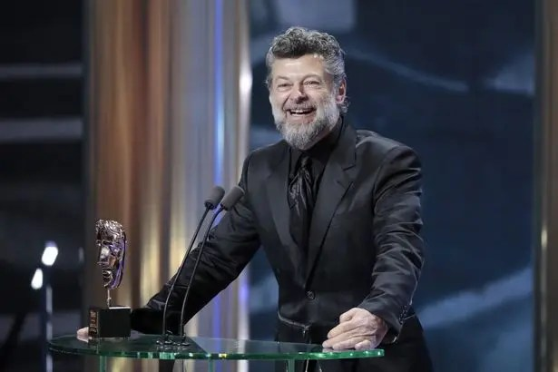 A man (Andy Serkis) with a grey beard in an all black suit, smiles as he stands at a see-through podium. Sitting on the podium is an award statue.