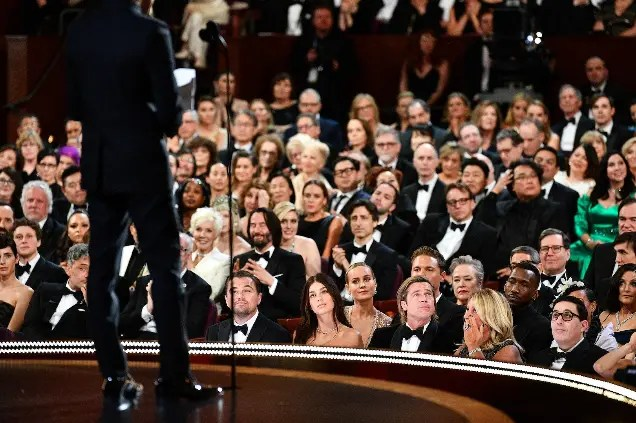 A figure in a black tuxedo addresses an audience of movie stars sat in their seats in a theatre.