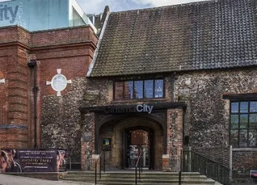 """A wide shot of the exterior of Cinema City: the left side of the building features orange brickwork and several film posters, the right hand side has stones protruding from the stone walls, and stone stairs leading up to wooden doors with a sign above saying """"Cinema City""""."""