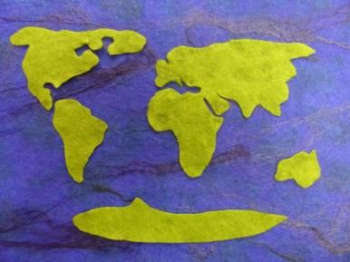 Zuerst wird der Untergrund als Fläche gefilzt (Vorfilz mit Seidenfäden), dann die ausgeschnittenen Kontinente aufgelegt...