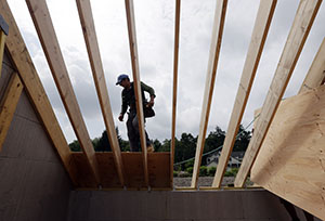 A worker installs a roof on a home last month in New Paltz, N.Y. (AP file photo)