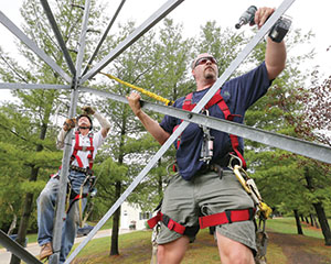 Charles Grell, left, and Aaron Lahman, both of Gone 2 Green, check the bolts on an 80-foot tower at a rural residence near Webster, Minn. (Staff photo: Bill Klotz)