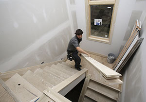 In this Nov. 11 photo, carpenter Will Hostetler carries trim downstairs at a home under construction by Larry Block Builders in Pepper Pike, Ohio. (AP photo: Tony Dejak)