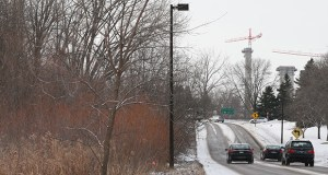 Cars pass the site of the future Southwest Light Rail Transit line's Opus Station, which is planned for Bren Road West and Bren Road East in the Opus Business Park in Minnetonka. Construction cranes working on the UnitedHealth campus are visible in the background. (Staff photo: Bill Klotz)