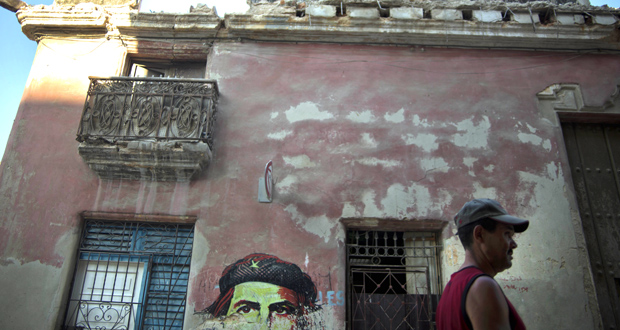 A man walks past a building April 12 that collapsed in heavy rain in Havana, Cuba. Despite reforms to address the island's housing problem, such building collapses remain common in Cuba. (AP Photo/Ramon)