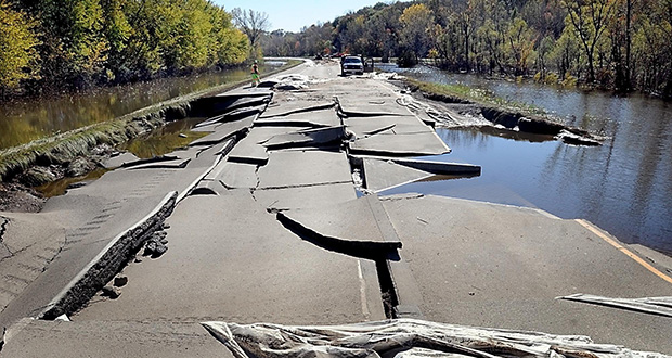 In this October 2010 file photo, Minnesota Department of Transportation crews remove temporary levees near a 140-foot section of northbound Highway 169 that collapsed in flooding near St. Peter, Minn. (AP photo: Mankato Free Press)