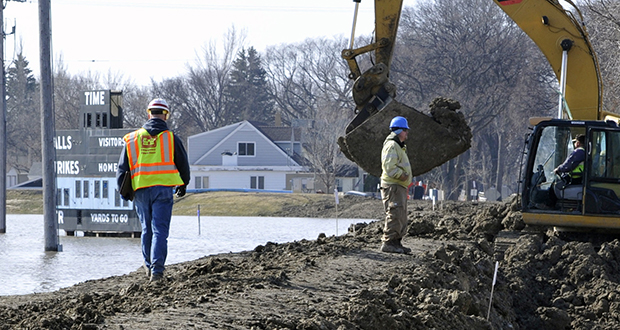 Bill Meier, left, an inspector with the U.S. Army Corp of Engineers, oversees work to shore up a levee next to the flooded Mickelson Park in Fargo, North Dakota, on Friday, April 8, 2011. (AP file photo)