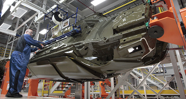 An assembly line worker works on a 2015 Chrysler 200 automobile at the Sterling Heights Assembly Plant in Sterling Heights, Mich. (AP photo)