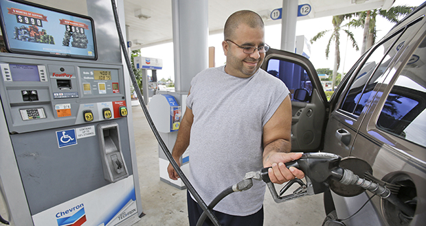 In this June 4 photo, Baltazar Rosado pumps gasoline into his car at a Chevron station in Pembroke Pines, Florida. Gasoline costs rose 3.3 percent in June. (AP photo)