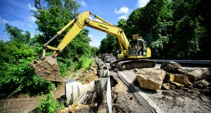 A Minnesota Department of Transportation crew clears a mudslide and places huge rocks around a washed-out culvert along Highway 66 on June 18 in Mankato. (Associated Press photo: Star Tribune, Glen Stubbe)