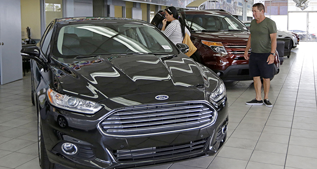 Potential customers check a Ford Fusion at a dealership in Hialeah, Florida. Demand for motor vehicles and parts climbed by 10.2 percent in July, the most since August 2009, according to the Commerce Department. (AP photo: Alan Diaz)