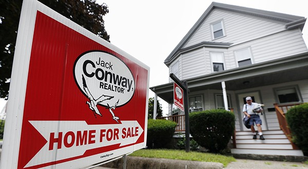 A postal carrier delivers mail to a house for sale in Quincy, Mass. Uncertainty in agency collateralized mortgage obligations could potentially hurt demand in part of the U.S. home-finance system. (AP file photo)