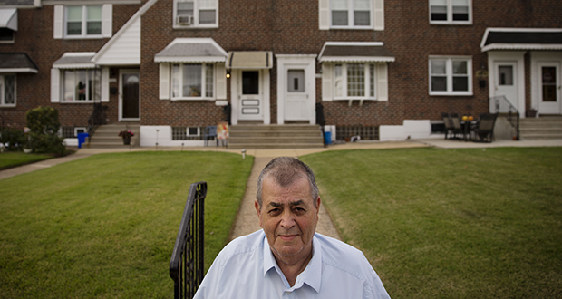 Myles Griffin, 74, stands in front of his home in Philadelphia on Sept. 11. Griffin has lived with his wife for 40 years in their three-bedroom row home and after retiring three years ago, the couple signed up for a reverse mortgage in May. (AP Photo: Matt Rourke)