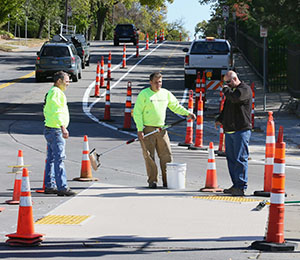Employees of Sir Lines-A-Lot work on constructing a bike lane on 36th Street South between Calhoun Parkway and Dupont Avenue in Minneapolis. Hennepin County and Minneapolis collaborated to add bike lanes and flexible posts to separate bikes and vehicles. (Staff photo: Bill Klotz)