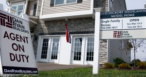 Signs welcome visitors to a model home Sept. 10 as construction is underway at a housing development in Zelienople, Pennsylvania. Real estate date provider CoreLogic reported Tuesday that increases in U.S. home prices slowed in August. (AP Photo: Keith Srakocic)