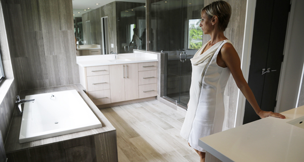 Mara Boccolini, a Realtor associate with South Beach Estates, shows the master bathroom Sept. 24 in a newly renovated waterfront property on the market during a viewing for brokers, in Miami Beach, Florida. Standard & Poor's released its S&P/Case-Shiller index of home prices Tuesday, showing home prices rose in September at the slowest pace in more than two years. (AP Photo: Lynne Sladky)