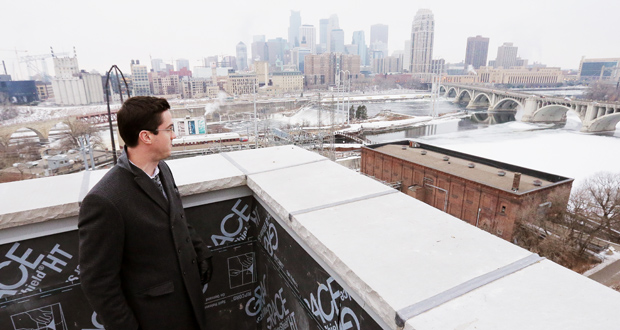 Dominium's Owen Metz points out the view from the rooftop amenity area at the A-Mill Artist Lofts, an affordable apartment rehabilitation project under construction at 301 Main St. SE in Minneapolis. Parts of the complex are already open, and the entire project should be complete by next summer. (Staff photo: Bill Klotz)