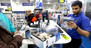 Best Buy employee Daruosh Habbir helps holiday shoppers check out goods Nov. 27 at Best Buy in Northbrook, Illinois. The Commerce Department reported Tuesday that U.S. consumer spending increased 0.6 percent in November. (AP File Photo)