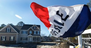 A flag flaps in the breeze Jan. 8 in front of a new home for sale in Richmond, Virginia. The Commerce Department reported Tuesday that sales of new homes climbed 11.6 percent in December. (AP Photo: Steve Helber)