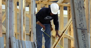 A worker measures before cutting Dec. 15 while working on the framing of a house under construction in Coppell, Texas. The Commerce Department reported Wednesday that U.S. housing starts slipped 2 percent in January. (AP Photo: LM Otero)