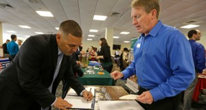 In this Friday, Feb. 6, 2015 photo, U.S. Marine Corps veteran Ignacio Yanes, left, writes information given by Jim Brooks, right, of the Small Business Administration at the annual Veterans Career and Resource Fair in Miami. (AP Photo: Alan Diaz)