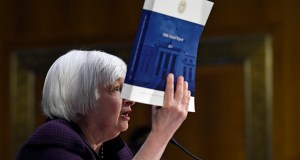 Federal Reserve Board Chair Janet Yellen holds up a copy of the 100th Annual Report from the Federal Reserve on Tuesday as she testifies on Capitol Hill in Washington, Tuesday, Feb. 24, 2015, before the Senate Banking Committee. (AP Photo/Susan Walsh)