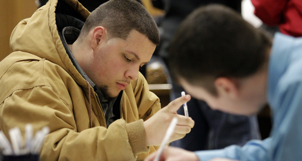 Tyler Kelly, 19, left, fills out applications for parking enforcement and environmental compliance jobs during a public safety job fair Jan. 29, 2015 at City Hall in Saginaw, Mich. (AP Photo)