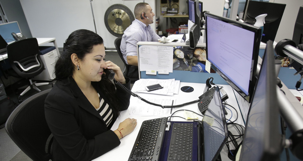 Karen Gonzales, a recruiter with Affinity Resources, a temporary staffing company, talks with a job seeker on the phone Monday from her Miami Lakes, Florida, office. Complying with the Affordable Care Act is costing small businesses like Affinity thousands of dollars that they didn't have to spend before the new regulations became law. (AP Photo: Wilfredo Lee)