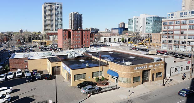 The House of Charity wants to build a new five-story, L-shaped affordable housing building on property currently occupied by the recently closed Finance & Commerce printing plant at 615 S. Seventh St. (white building, right foreground) and House of Charity's existing Food Centre at 714 Park Ave. S. (red brick building, left background), as seen from the Hennepin County Medical Center parking ramp. (Staff photo: Bill Klotz)