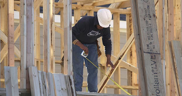 A worker measure before cutting Dec. 15, 2014, while working on the framing of a house under construction in Coppell, Texas. (AP file photo)