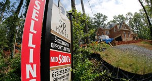 A realty sign is posted in front of a new home under construction June 4 in Roswell, Georgia. Standard & Poor's reported Tuesday that its S&P/Case-Shiller home price index climbed 4.9 percent in May. (AP Photo: John Bazemore)
