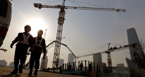 Workers walk out from a construction site Jan. 20 at the Central Business District of Beijing, China. Otis elevator, which has staked much on increasing urbanization and soaring skyscrapers in cities across China, is struggling with declining revenue in 2015 as China's economy sours. (AP File Photo)