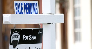 "A ""sale pending"" sits atop a realty sign Jan. 8 outside a home for sale in Surfside, Florida. The National Association of Realtors reported Thursday that pending sales edged up in July. (AP file photo)"
