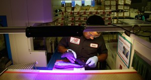 Elder Brandao, working July 1 under ultraviolet lights, glues an outsole to a midsole of the New Balance proposed 950v2 sneaker at one of company's manufacturing facilities in Boston. The Institute for Supply Management said Tuesday that U.S. manufacturing expanded slowly in August. (AP file photo)