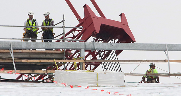 "Workers walk across the north side of U.S. Bank Stadium's roof on Wednesday. Last week a worker died after he ""broke through a guardrail"" and fell onto a platform, according to OSHA. Another worker was injured when he struck a post. (Staff photo: Bill Klotz)"